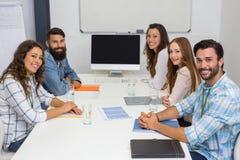 微笑的执行委员画象在会议室在会议期间 免版税库存图片