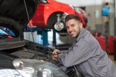 微笑的技工在汽车修理店 免版税库存照片