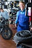 微笑的技术员供以人员与摩托车的轮子一起使用 库存图片