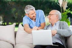 微笑的护士和使用膝上型计算机的老人 库存照片