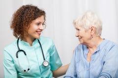 微笑的护士和愉快的年长夫人 免版税图库摄影