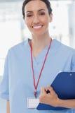 微笑的护士待办卷宗和看照相机 库存图片