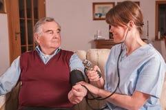 微笑的护士测量的血压 免版税库存图片
