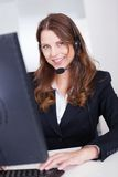 微笑的招待员或呼叫中心工作者 库存图片