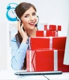微笑的操作员位子在与红色礼物盒的桌上 愉快的busines 免版税库存图片