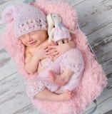 微笑的新出生的女婴用玩具野兔 免版税库存照片