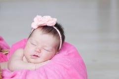 微笑的新出生睡觉在与被编织的花的篮子在头,女婴说谎在桃红色毯子的,逗人喜爱的孩子 库存图片