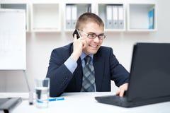 微笑的新商人联系在移动电话 库存照片