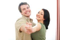 微笑的新夫妇跳舞在家 免版税库存图片