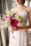 微笑的新娘的中央部位在家拿着花束的婚礼礼服的 库存照片