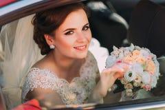 微笑的新娘的特写镜头画象有坐在汽车的五颜六色的花束的 图库摄影