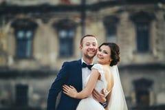 微笑的新婚佳偶在一座老城堡的前面拥抱 库存图片