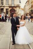 微笑的新婚佳偶在电车轨道摆在某处在老城市 免版税库存图片