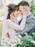 微笑的新婚佳偶是拥抱和抚摸每cheel 旁边特写镜头画象 免版税图库摄影