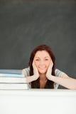 微笑的新学员在有书的一间教室 免版税库存图片