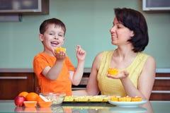 微笑的新母亲和儿子烘烤松饼 库存照片