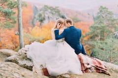 微笑的新郎在被染黄的森林里时接触愉快的新娘的头,当坐岩石 免版税库存照片