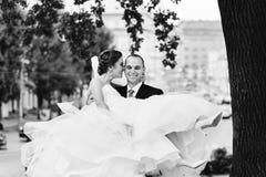 微笑的新郎运载壮观的礼服的新娘在他的胳膊 免版税库存照片