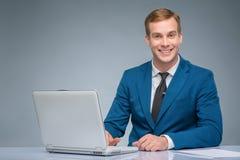 微笑的新闻记者与他的膝上型计算机一起使用 免版税库存图片
