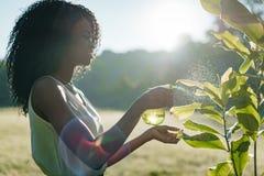 微笑的旁边画象相当使用绿色塑料触发器浪花的非洲女孩为室外的植物在被日光照射了 库存图片