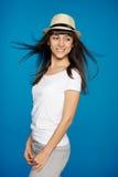 微笑的无忧无虑的妇女佩带的白色草帽 免版税库存图片