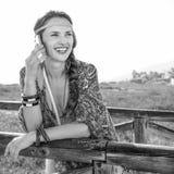 微笑的时尚吉普赛样式女孩户外谈话在手机 免版税图库摄影