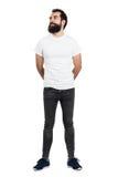 微笑的有胡子的人佩带的白色的T恤杉和看紧的牛仔裤  免版税库存照片
