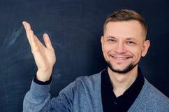 微笑的有胡子的人做一个受欢迎的姿态用一只开放手 免版税图库摄影