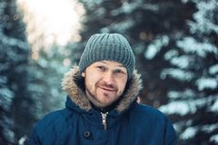 微笑的有胡子的人旅客林务员猎人画象在冬天森林里 免版税图库摄影