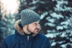 微笑的有胡子的人旅客林务员猎人画象在冬天森林里 免版税库存图片