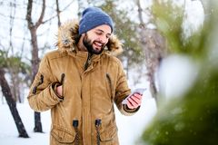 微笑的有胡子的男服温暖的冬季衣服和使用有快速的互联网数据连接的智能手机在国家边 库存照片