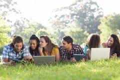 微笑的朋友在使用片剂个人计算机和膝上型计算机的公园 库存图片