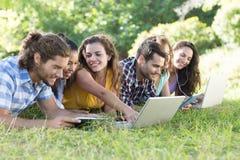 微笑的朋友在使用片剂个人计算机和膝上型计算机的公园 库存照片