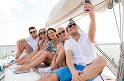 微笑的朋友坐游艇甲板 免版税图库摄影