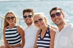 微笑的朋友坐游艇甲板 库存图片