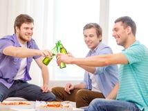 微笑的朋友用停留的啤酒和的薄饼 免版税图库摄影