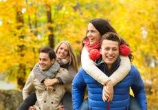 微笑的朋友获得乐趣在秋天公园 库存图片