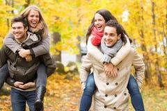 微笑的朋友获得乐趣在秋天公园 免版税图库摄影