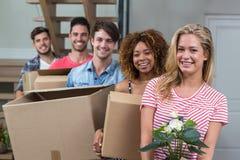 微笑的朋友,当运载箱子在新房里时 免版税库存图片