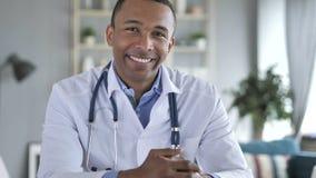 微笑的正面非裔美国人的医生At在照相机的Work Looking 库存照片