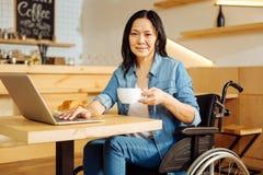 微笑的残疾妇女饮用的咖啡 库存图片