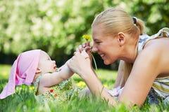 年轻母亲使用与她的草的婴孩 免版税库存图片