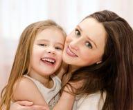 微笑的母亲和一起使用她的小女孩 库存图片