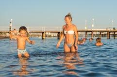 年轻微笑的母亲和使用在天时间的海滩的男婴儿子 库存照片