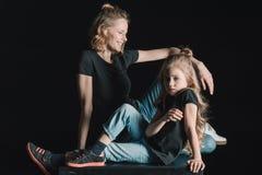 微笑的母亲和女儿坐在黑色的立方体 库存图片