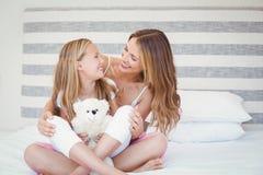 微笑的母亲和女儿坐床 免版税库存图片