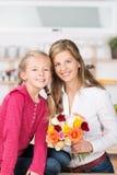 微笑的母亲和女儿有一束的玫瑰 免版税库存图片
