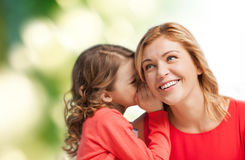 微笑的母亲和女儿耳语的闲话 库存图片