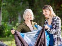 微笑的母亲和女儿聚集的帐篷  免版税图库摄影