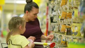 微笑的母亲和女儿超级市场的 女儿帮助她的母亲选择一个橡皮膏 Cutie女儿 股票录像